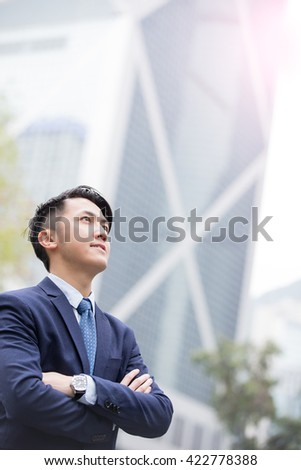 Business man smile look sky with business office building background, asian, shot in Hong Kong - stock photo