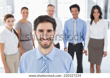 Business man smiling at camera with co-workers behind him - stock photo