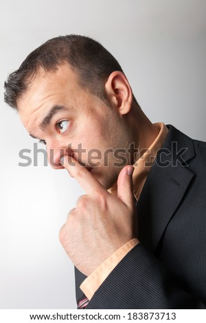 Business man sneaking his finger up his nose.
