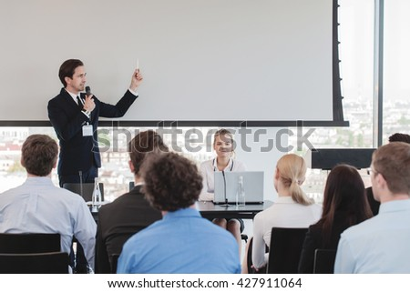 Business man speaking at presentation in microphone in office - stock photo