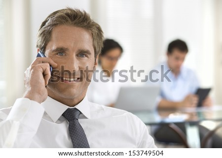 Business man speaking on the cell phone while in a meeting, looking camera - stock photo