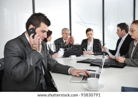 Business man speaking on the phone and typing on laptop while in a meeting