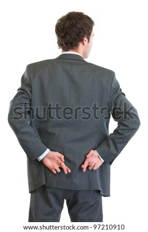 Business man standing back to camera with crossed fingers - stock photo