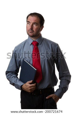 Business man standing holding a note book looking to the side - stock photo