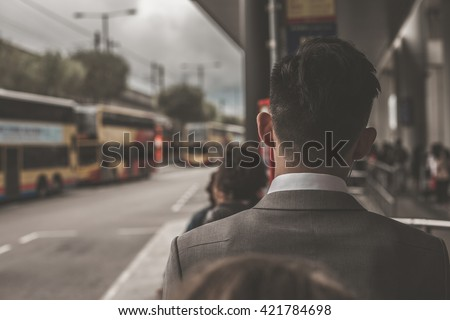 Business man standing in a queue at bus stop, view from the back. Bus terminal near international airport in Hong Kong, China. - stock photo
