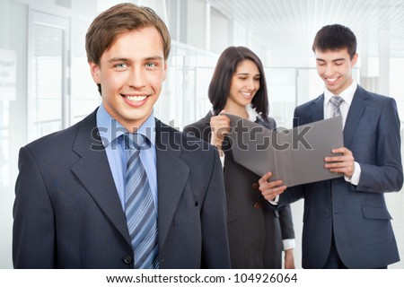 Business man standing in front of her colleagues - stock photo