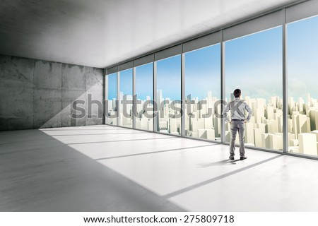 business man standing inside an office building looking outside - stock photo
