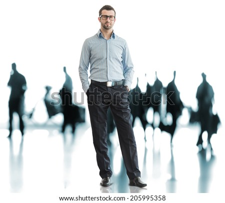 Business man standing on airport with traveling people in background - stock photo