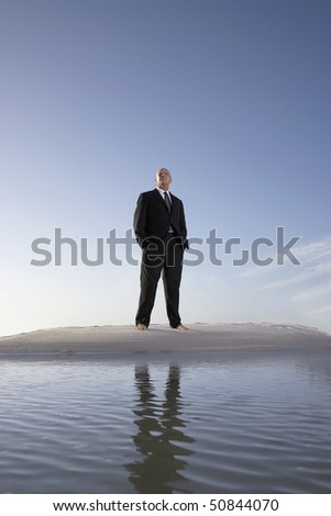Business man standing on beach, portrait, low angle view