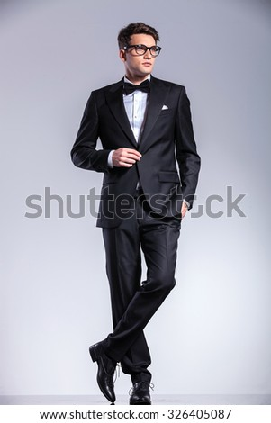 Business man standing on studio background with his legs crossed while opening his jacket.