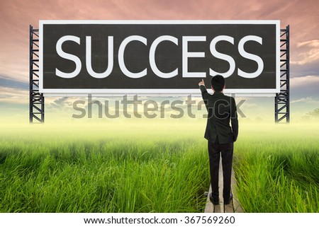 business man standing on wood bridge between rice field and pointing with large sign of success (business concept) - stock photo