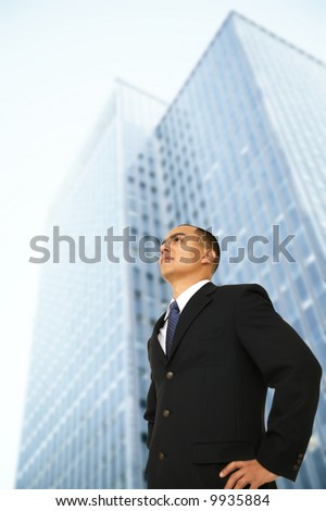 business man standing outdoor in front of tall squared business building - stock photo