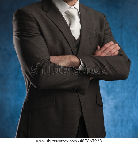 Business man standing with his arms crossed, on a blue background, stock picture