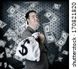 Business man stowing away cash inside bank vault when hording away finance money bag with greedy expression - stock