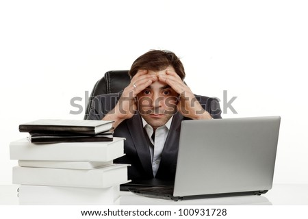 Business man stressed out in his office with a lap top and a lot of papers in front of him holding his head and looking in one spot