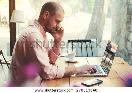 Business man talking on smart phone and look to laptop screen, male freelancer working on computer at wooden table of modern coffee shop loft, young hipster having conversation on cell phone, filter - stock photo