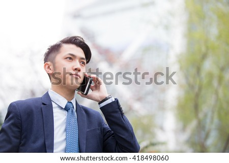Business man talking on smart phone with business office building background, asian - stock photo