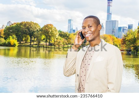 Business man talking on the phone. Dressing in cream blazer, collarless sweater, a young black guy is standing by a lake in a big city, smiling, making a phone call on his mobile phone.  - stock photo