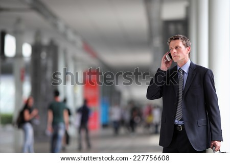 business man talking on the phone in the crowd - stock photo