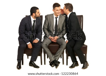 Business man telling a secret to a colleague while other trying to listen and sitting all on chiars isolated on white background