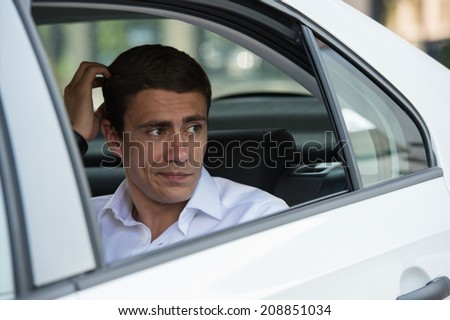 Business man thinking on back seat of his car - stock photo