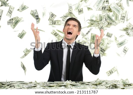 Business man throwing dollar bills and yelling. Young businessman sitting with money in office