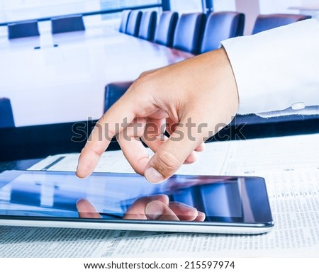 business man touch digital tablet on business newspaper in the office - stock photo