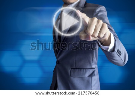 Business man touch play icon on blue background. - stock photo