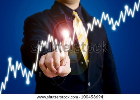 Business man touching a graph of stock market - stock photo
