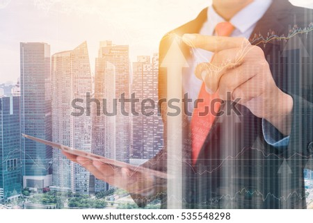 business man Trading concept using the tablet with financial graph on cityscape background, Double exposure style.