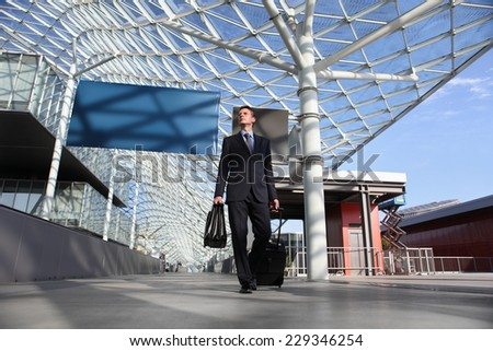 Business man travel work look the sign board walking with luggage trolley - stock photo