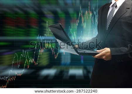 Business man typing on a modern laptop with stock market graph background