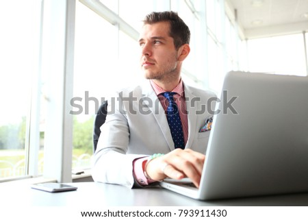 business man typing on laptop keyboard in office