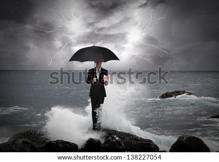 Business man under an umbrella standing on a rock in the sea with lightning sky, business concept - stock photo