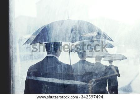 business man under rain walking on the street - stock photo