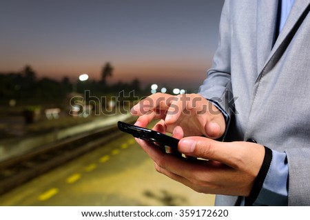 Business Man use Mobile Phone in Railway Station at Dawn - stock photo