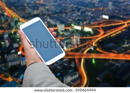 Business man uses her smart phone on city background. - stock photo