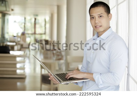 Business man using a laptop computer in the office - stock photo