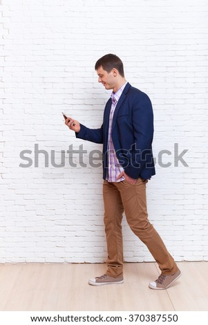 Business Man Using Cell Phone Smartphone Busy Walking Social Network Communication Full Length Over White Brick Wall - stock photo