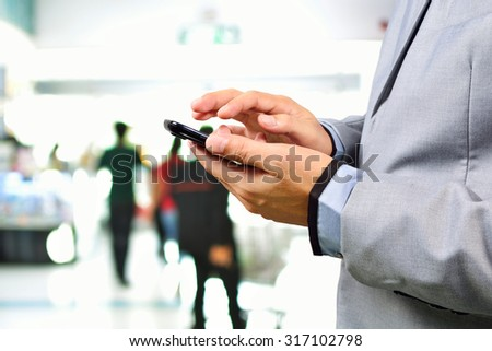 Business man using cellphone or Smartphone in Public Place - stock photo