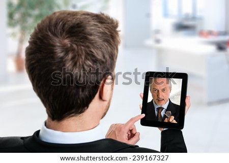 Business man using his tablet to speak to a colleague