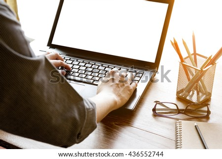 business man using laptop computer with blank white screen on office desk - stock photo