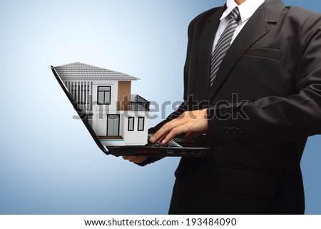 Business man using laptop with house model house concept in the hand - stock photo
