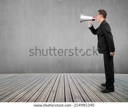 Business man using megaphone yelling with concrete wall wooden floor background - stock photo