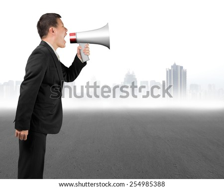 Business man using megaphone yelling with gray cityscape background - stock photo
