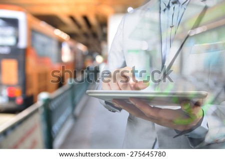 Business Man using Mobile Digital tablet in Bus Station as Time Management with Wireless Device Concept  - stock photo