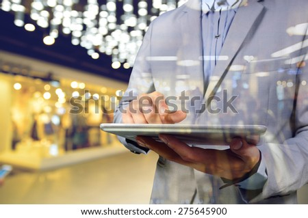 Business Man using Mobile Digital Tablet in the Modern Shopping Mall. Selective focus on Tablet as Communication Technology concept. Blue Colot tint in this image. - stock photo