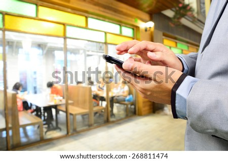 Business man using mobile smart phone in Restaurant or Food Court Plaza - stock photo