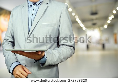 Business Man using Mobile Tablet in Gallery Art Center or Museum.  Selective Focus on Tablet and Hand. - stock photo