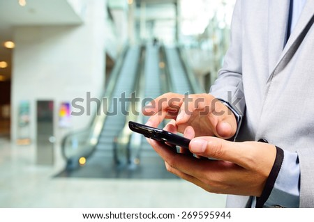 Business Man Using Mobile while going down Escalator - stock photo